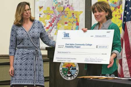 Stephanie Cook of the Idaho National Laboratory presents a research donation to Idaho Falls Mayor Rebecca Casper during a news conference announcing the city's community college citizen study panel. Kevin Trevellyan /ktrevellyan@postregister.com